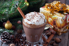 Hot chocolate with whipped cream in a glass. On a wooden background Stock Image