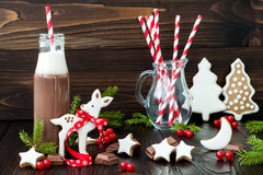 Hot chocolate with whipped cream in old-fashioned retro bottles with red striped straws. Christmas holiday drink and gingerbread Royalty Free Stock Photo