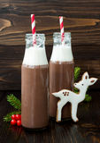Hot chocolate with whipped cream in old-fashioned retro bottles with red striped straws. Christmas holiday drink and gingerbread. Baby deer or fawn cookies Royalty Free Stock Photography