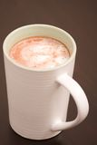 Hot chocolate in a white cup. A single cup of foaming hot chocolate standing on a table Royalty Free Stock Photography