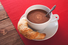 Hot chocolate in a white cup with a croissant on a wooden table. Hot chocolate in a white cup Royalty Free Stock Photo