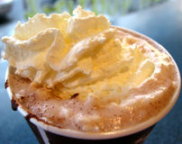 Hot chocolate with wipped cream, closeup. Hot chocolate with wipped cream in a paper cup, closeup Royalty Free Stock Photography