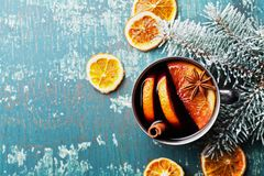 Hot christmas mulled wine or gluhwein with spices and orange slices on vintage teal table top view. Traditional drink on winter. Stock Images