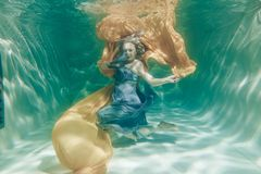 Hot Chubby Curvy Woman Posing Under water in beautiful clothes alone in the deep royalty free stock photo