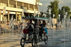 Hot city. Four young people ride in kind of car managed like bicycle through the fountains in Museon Park near the Gorky Central Park of Culture and Leisure in Stock Photography