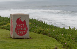 Hot Coals Only Bin on Green Cliff Stock Image