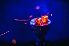 Hot coals on the bowl of the hookah with sparks for a traditional Eastern relaxation and enjoyment Stock Photo