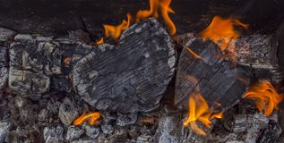 Hot coals and burning woods in the form of human heart. Glowing and flaming charcoal, bright red fire and ash. .Close-up stock photography