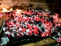 Hot coals in the fire. Beautiful image moving bonfire made wooden planks grid brick fireplace spark barbecuegrill design dark cooking bright yellow burn stock images
