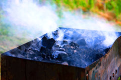 Hot coals with smoke Royalty Free Stock Photo