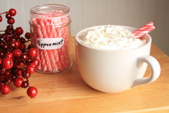 Hot coco with peppermint sticks jar with a cranberry wreath Stock Image