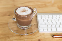 Hot cocoa chocolate drink with computer keyboard and pen Stock Photography