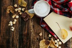 Hot cocoa coffee with popcorn, apple, cakes, leaves on the old Royalty Free Stock Image