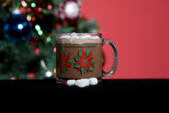 Hot Cocoa and Holiday Tree. Mug of hot cocoa with marshmellows in front of christmas tree Stock Images