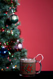 Hot Cocoa and Holiday Tree. Mug of hot cocoa with marshmellows in front of christmas tree Royalty Free Stock Photo
