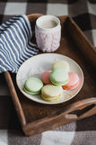 Hot cocoa in knitted cover and colorful macaroons Royalty Free Stock Photo
