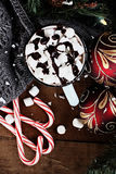 Hot Cocoa with Marshmallows and Chocolate Sauce. Christmas ornaments and candy canes in background. stock image