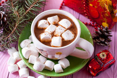 Hot cocoa with marshmallows on pink background. On a wooden board Royalty Free Stock Images