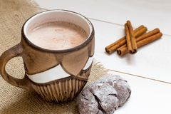 Hot cocoa with milk in brown cup, cinnamon sticks on white wooden table, close up stock photo