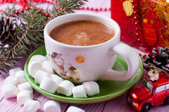 Hot cocoa on pink background. On a wooden board Stock Photos