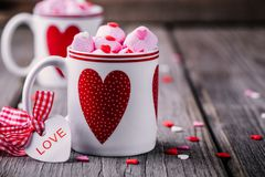 Hot cocoa with pink marshmallow in mugs with hearts for Valentine day. Hot cocoa with pink marshmallows in mugs with hearts on a wooden background for Valentine royalty free stock photos