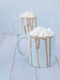 Hot cocoa in two white ceramic mugs. With marshmallow topping Royalty Free Stock Photos