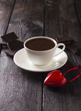 Hot cocoa in a white mug with slices of chocolate and red heart.  Stock Photo