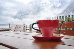 Hot coffe on a snowy day. Relaxing moment with a hot cup of coffee, on a table, at an Austrian restaurant, in Hallstatt, with a view over the Dachstein Mountains stock image