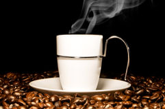 Hot coffee. Over coffee beans Stock Images