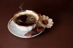 Hot Coffee. The cup of coffee with chocolate on brown background royalty free stock images