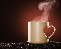 Hot coffee. Mug of hot coffee on coffee beans with rising steam Royalty Free Stock Photo