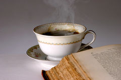 Hot Coffee. Cup of Hot Steaming Coffee and Old Book stock images