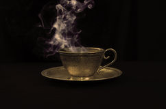 Hot coffee. In gold antique cup, and smoke above Stock Image