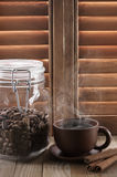 Hot coffee against shutters Stock Photos