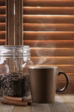 Hot coffee against shutters Royalty Free Stock Photography