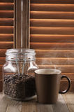 Hot coffee against shutters Royalty Free Stock Images