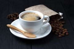 Hot coffee with anise, a wooden spoon and a bag of coffee beans Stock Photo