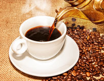 Hot coffee from arabic copper turks and  scattered coffee Royalty Free Stock Photography