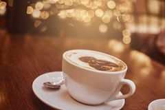 Hot coffee with art in a cup on the wooden table in a coffee shop, blur background with bokeh effect royalty free stock photo