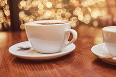 Hot coffee with art in a cup on the wooden table in a coffee shop, blur background with bokeh effect stock photos