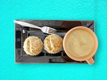 Hot coffee with  banana cupcakes on black dish on blue cement table background Stock Images