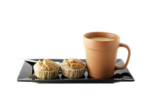Espresso hot coffee with milk in brown ceramic cup and banana cupcakes with fork on black dish isolated on white background. Beverage and sweet dessert for Stock Images