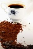 Hot coffee and beans. Hot coffee in a cup and roasted coffee beans and ground coffee Stock Image