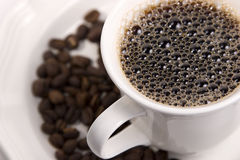 Hot Coffee and Beans. Cup of hot Black Coffee on a saucer of whole beans with selective focus on bubbles Stock Images