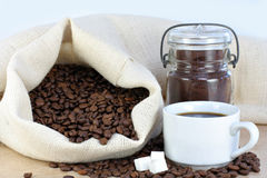 Hot coffee, beans and sugar cubes. Royalty Free Stock Image