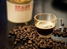 Hot coffee and coffee beans. On wooden background Royalty Free Stock Photo