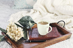 Hot Coffee in Bed. A hot relaxing cup of coffee with a book and flowers in a serving tray sitting on a comfortable bed with blanket. Extreme shallow depth of stock photography