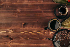 Hot coffee in black cup with beans, dry leaves and turkish pot cezve with copy space on brown old wooden board background, top vie Royalty Free Stock Image