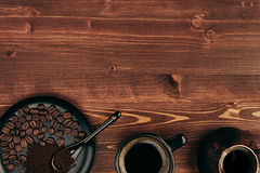 Hot coffee in black cup with beans, spoon and turkish pot cezve with copy space on brown old wooden board background, top view. Royalty Free Stock Photo