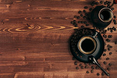 Hot coffee in black cup with beans, spoon and turkish pot cezve with copy space on brown old wooden board background, top view. Royalty Free Stock Images